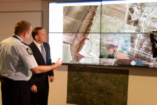 Tony Abbott inspects an aerial view of the MH17 crash site